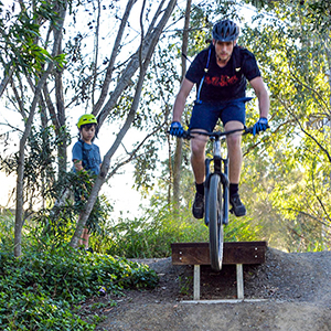 An image of Ethan Martin, of Mt Warren Park, going over a jump at the new Tudor Park mountain bike track at Loganholme.