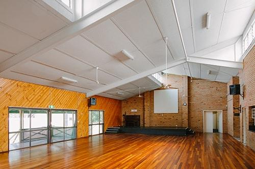 large hall with brick walls and wooden floors. small stage at front of room.