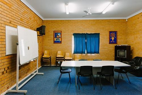 brick rom with blue carpet. small tabe and white boards