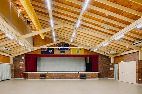 Brick room with exposed beams. stage at front of room with red curtains
