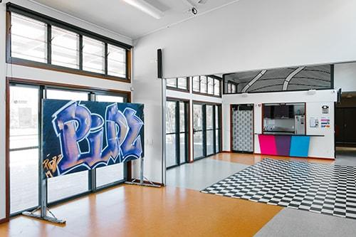open space with checkerboard floor and blackboard with artistic graffiti