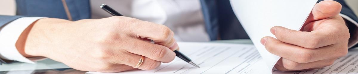 Picture of a man signing a document