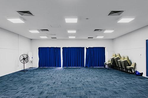 White room with blue carpet and curtains, chairs piled in far corner.