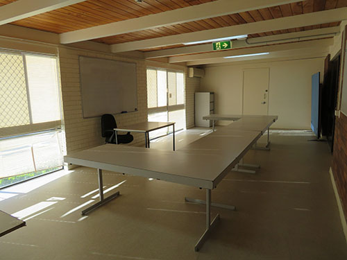 White tables set out in U shape in centre of a small room
