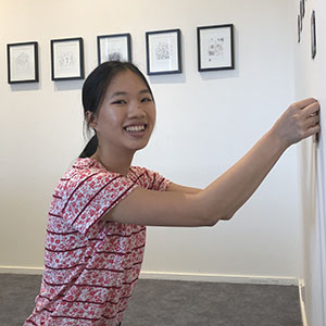 Hanging her work at the Logan Art Gallery is young artist Teresa Poon.