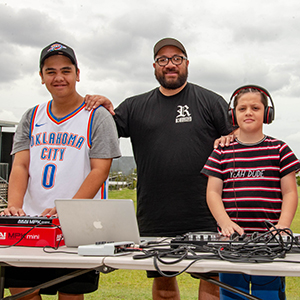 Man standing between two teenage boys who are operating DJ equipment.
