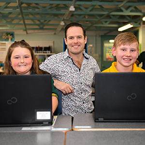 An image of City of Logan Deputy Mayor Jon Raven accessing the internet with Marsden State School students Marie Ash, of Waterford West, and Jess Obersteller, of South Maclean, who both have laptops.