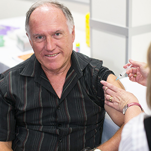 An image of a man in Logan getting an influenza shot as vaccines delivered by Council achieve record levels.