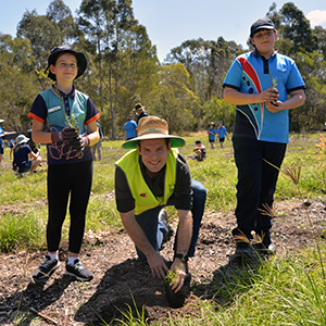 An image of Logan City Council Deputy Mayor Jon Raven planting an endangered Melaleuca irbyana sapling with Yarrabilba students Charlotte Sulja (left) and Angela Maroske-Barton at Moffatt Park in Waterford West.