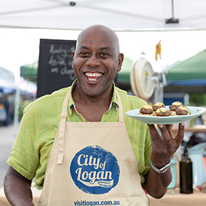 An image of Celebrity TV chef Ainsley Harriott holding a plate of food at Logan's weekly Global Food Markets.