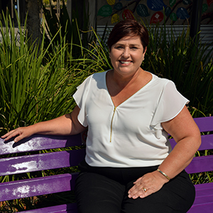An image of Logan City Council Division 12 Councillor Karen Murphy sitting on the city's first purple bench in Beenleigh Town Square.