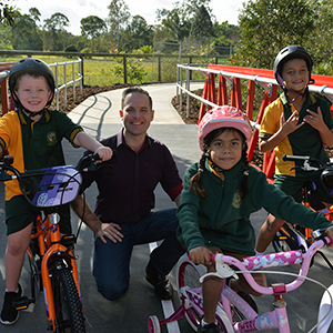 A photograph of  Logan City Council Deputy Mayor Jon Raven with Oscar Ferguson, 7, Jade Green, 7, and Kodi Wills, 8, from Marsden State School, on the mini 'Logan Red Bridge' at the Demeio Park cycle safety circuit which opened in Marsden today.