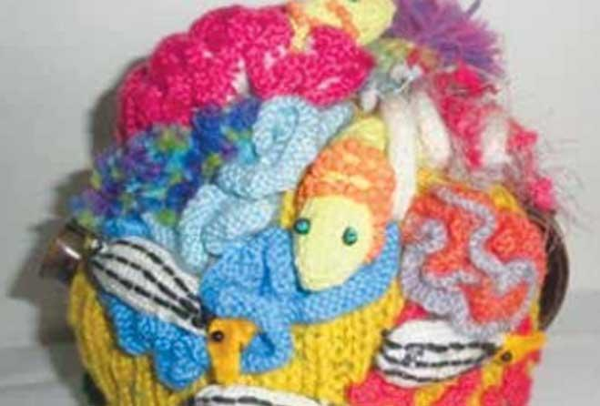 Colourful knitted tea cosies.