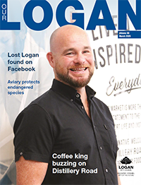 Our Logan magazine cover for March 2020. Cover shows a young smiling man in smart casual shirt with the caption Coffee king buzzing on distillery road.